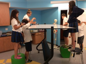 6th grade students use available tools, here a white board to test their robot's path of making a perfect square.